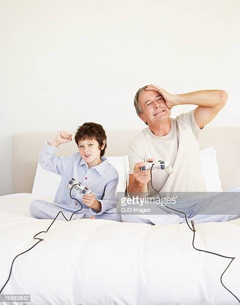 Un grand-père jouant à des jeux vidéo avec son petit-fils au lit