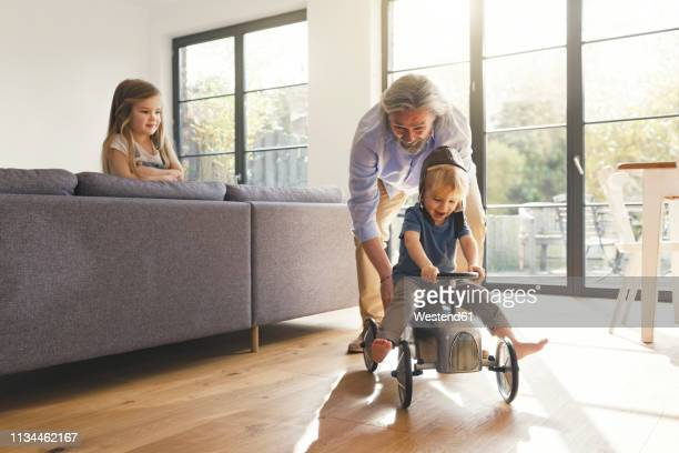 grandfather playing with grandchildren, sitting on toy car - jouer photos et images de collection
