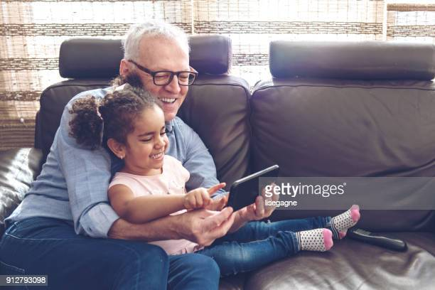 grandfather playing with granddaughter on a mobile - grandparent stock pictures, royalty-free photos & images
