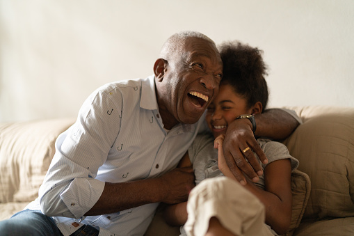 Grandfather Playing with Her Granddaughter at Home 1087914082