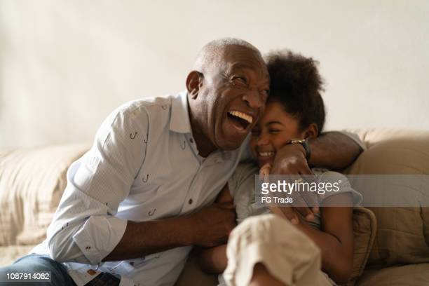 grandfather playing with her granddaughter at home - african american family home stock photos and pictures