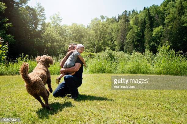 Grandfather playing with toddler and dog outdoors in summer.