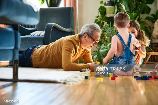 grandfather playing with wooden blocks with boy and girl - playing stock pictures, royalty-free photos & images