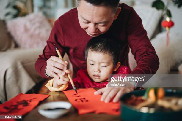 grandfather practising chinese calligraphy for chinese new year fai chun (auspicious messages) and teaching his grandson by writing it on a piece of red paper - tradition stock pictures, royalty-free photos & images