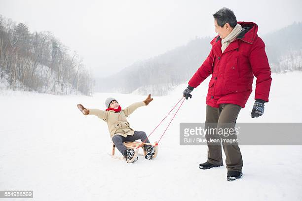 Grandfather pulling grandson on sled