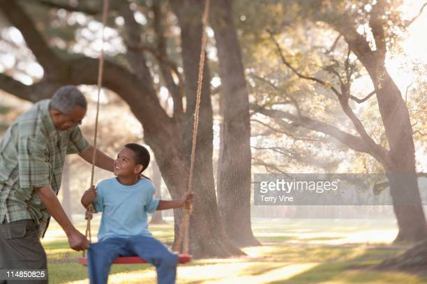 Grandfather pushing grandson on swing