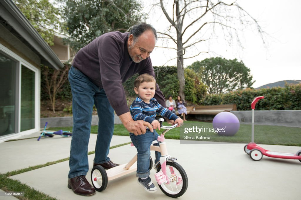 Grandfather pushing grandson on tricycle : Stock Photo