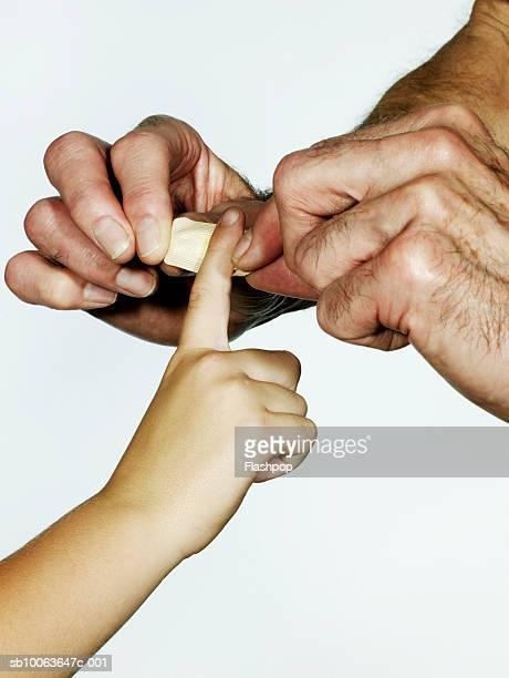 Grandfather putting plaster on grandson's (6-7) finger, close-up