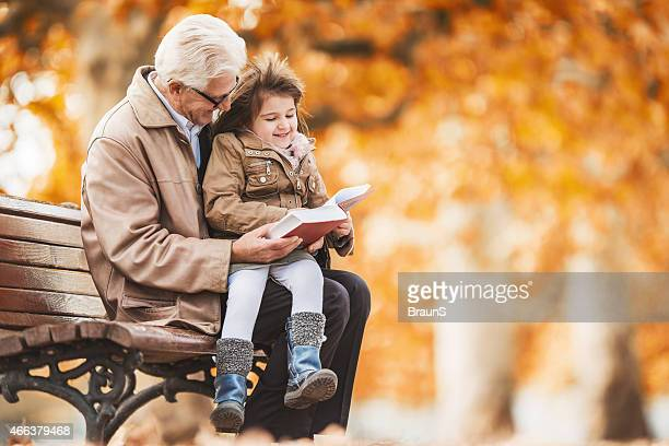 Grandfather reading a book to little girl in the park.