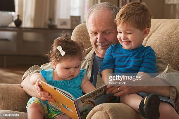 nonno lettura libro per nipoti - fratello foto e immagini stock