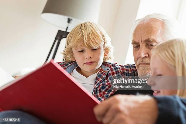 Grandfather reading book to grandchildren