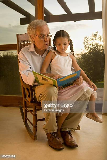 grandfather reading to his granddaughter - lap body area stock photos and pictures