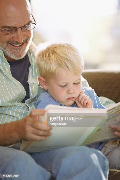 Grandfather reading to his grandson