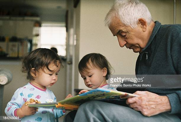 Grandfather Reading to Twin Granddaughters