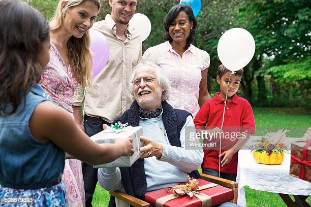 grandfather receiving gifts on birthday party in garden - homme maghrebin photos et images de collection