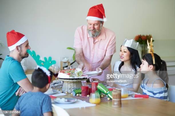 ダイニング テーブルで彼の家族にクリスマス ・ パブロバを提供の祖父 - オーストラレーシア ストックフォトと画像