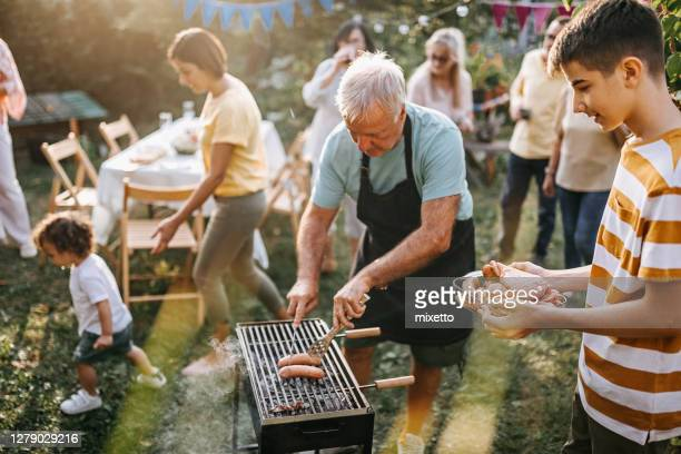 grandfather serving sausage to teen grandson - weekend activities stock pictures, royalty-free photos & images