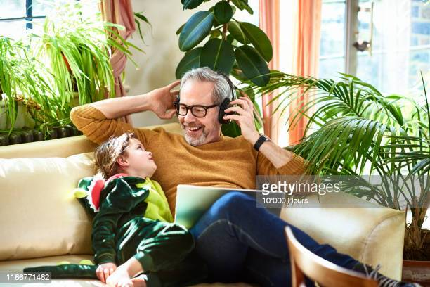 grandfather sharing headphones with cute girl on sofa - active seniors stock pictures, royalty-free photos & images