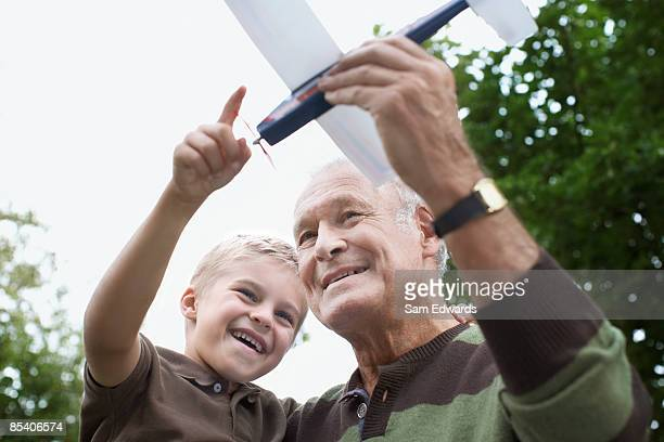 Grandfather showing grandson toy airplane