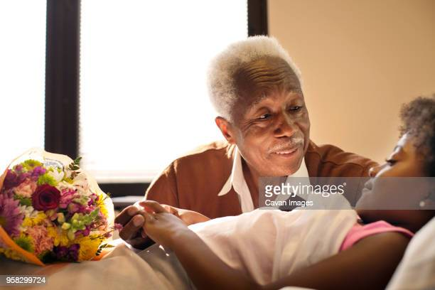 Grandfather sitting by girl on bed in hospital