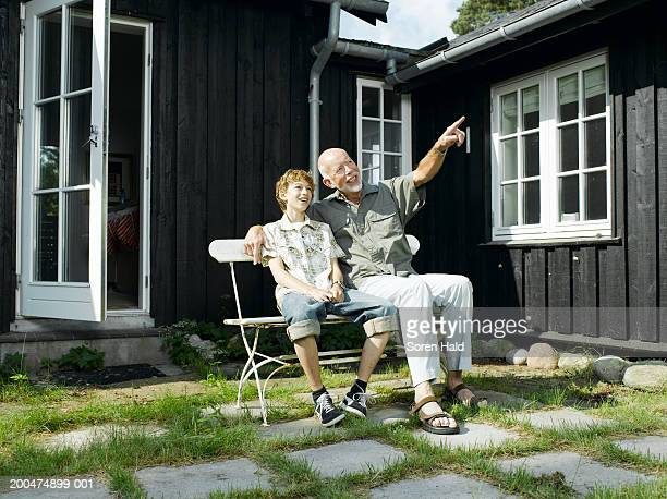 Grandfather sitting in garden with grandson (10-12) pointing upwards