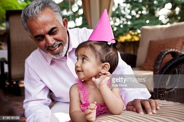 Grandfather sitting with granddaughter at birthday party