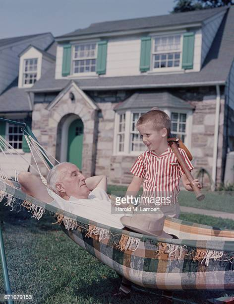 grandfather sleeping in hammock and grandson holding baseball bat  - {{relatedsearchurl(carousel.phrase)}} fotografías e imágenes de stock