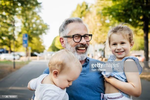 grandfather smiling while holding grandchildren - くわえる ストックフォトと画像