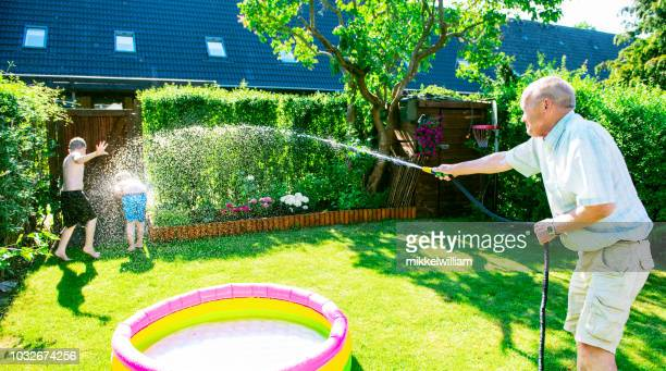 Grandfather sprays water on grandchildren with garden hose for fun