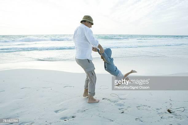 Grandfather swinging boy on beach