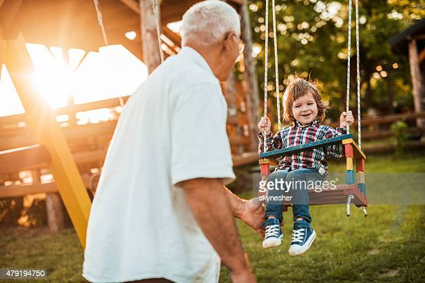 Grandfather swinging his happy grandson at sunset.