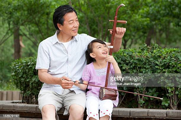 Grandfather teaching Chinese traditional musical instrument Erhu