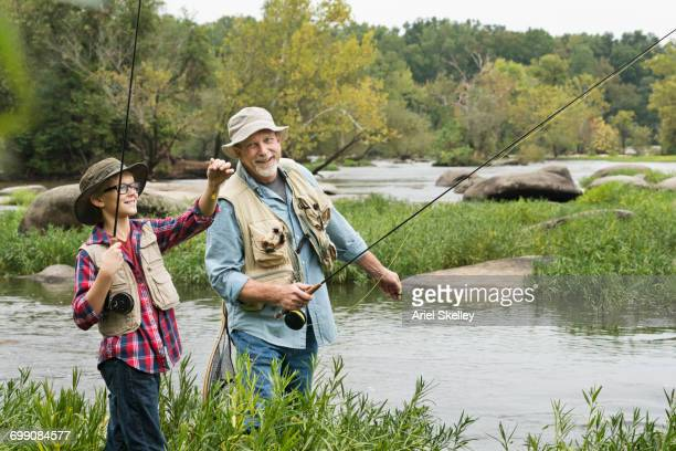 grandfather teaching fishing to grandson - fishing tackle stock pictures, royalty-free photos & images