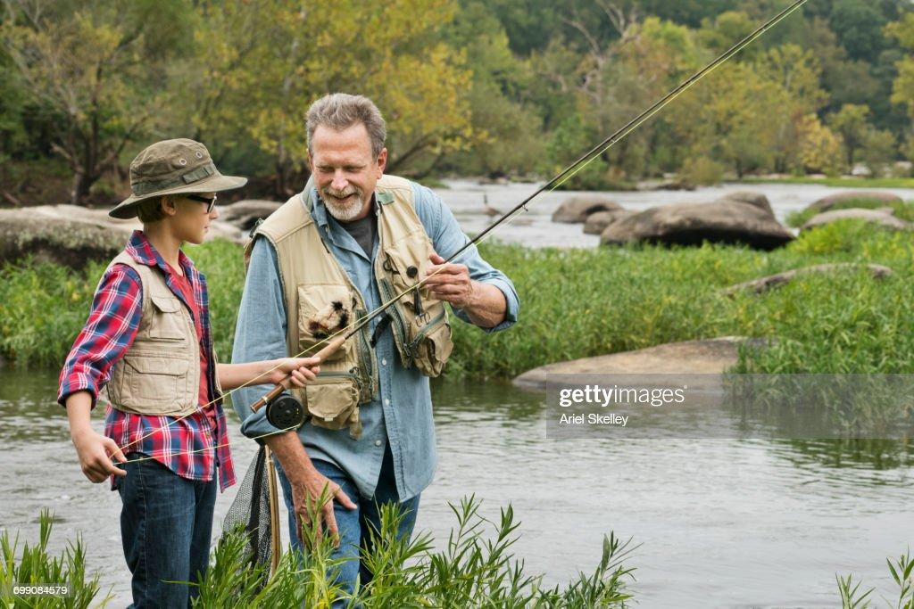 Grandfather teaching fishing to grandson : Stock Photo