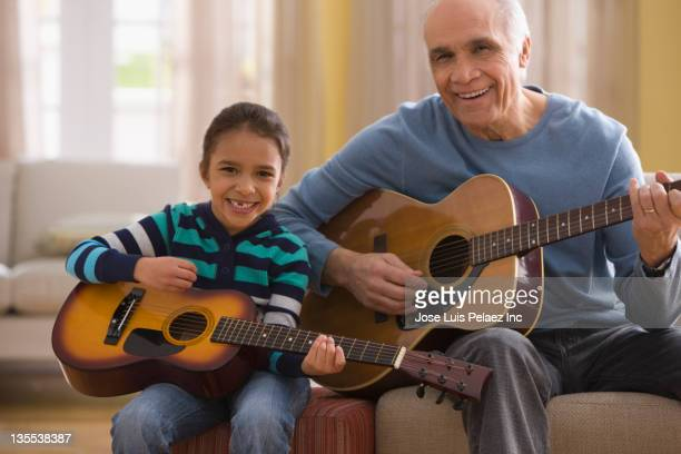 grandfather teaching granddaughter how to play guitar - 爪弾く ストックフォトと画像