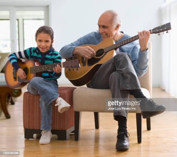 grandfather teaching granddaughter how to play guitar - ottomane stockfoto's en -beelden