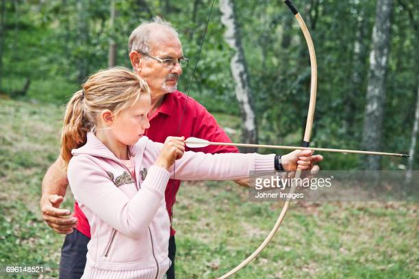 Grandfather teaching granddaughter shooting bow