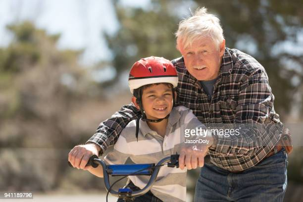 grandfather teaching grandson bicycle riding - first occurrence stock pictures, royalty-free photos & images