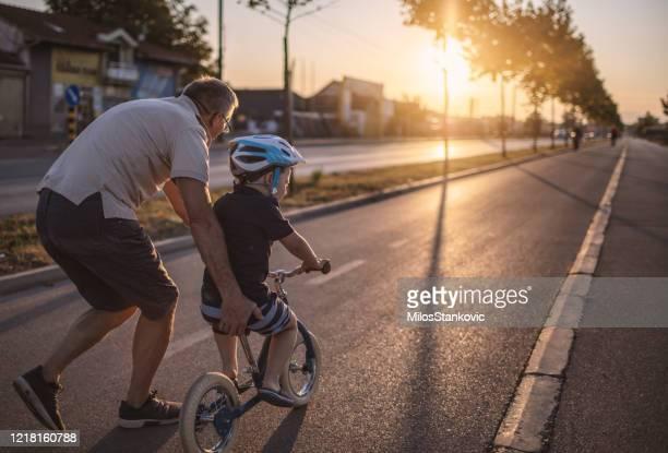 nonno che insegna al nipote in bicicletta - incoraggiamento foto e immagini stock
