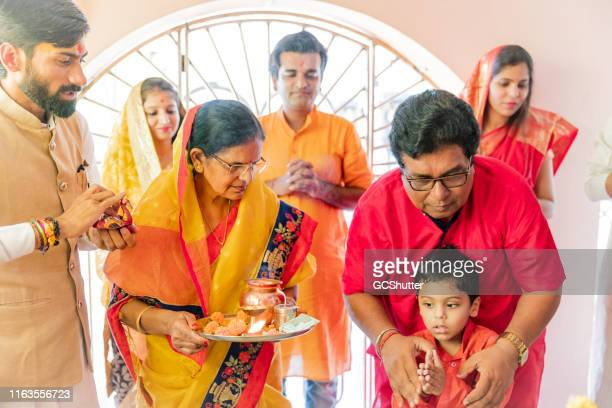 grandfather teaching grandson how to pray at a hindu temple - hinduism stock pictures, royalty-free photos & images