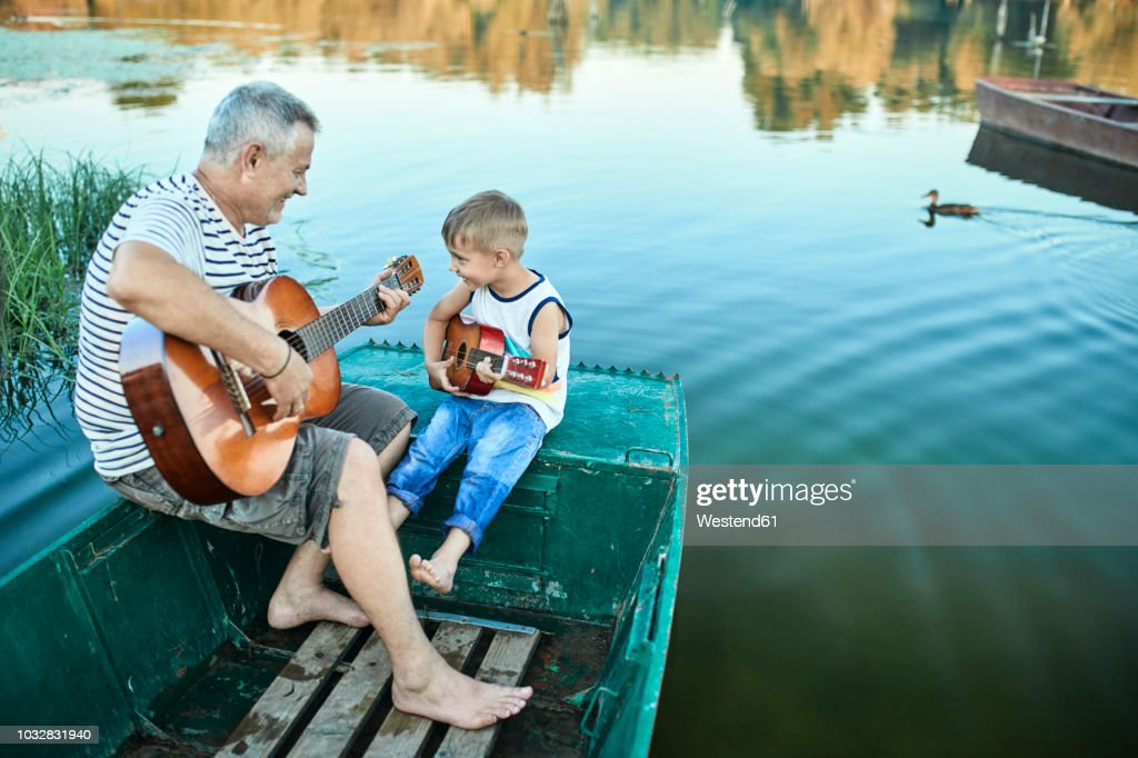 Grandfather teaching grandson playing guitar : Stock Photo