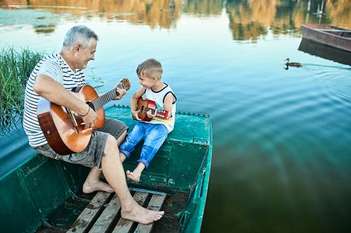 Grandfather teaching grandson playing guitar - gettyimageskorea