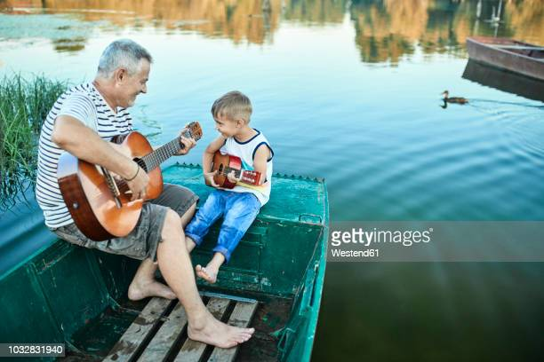 grandfather teaching grandson playing guitar - grandfather stock pictures, royalty-free photos & images