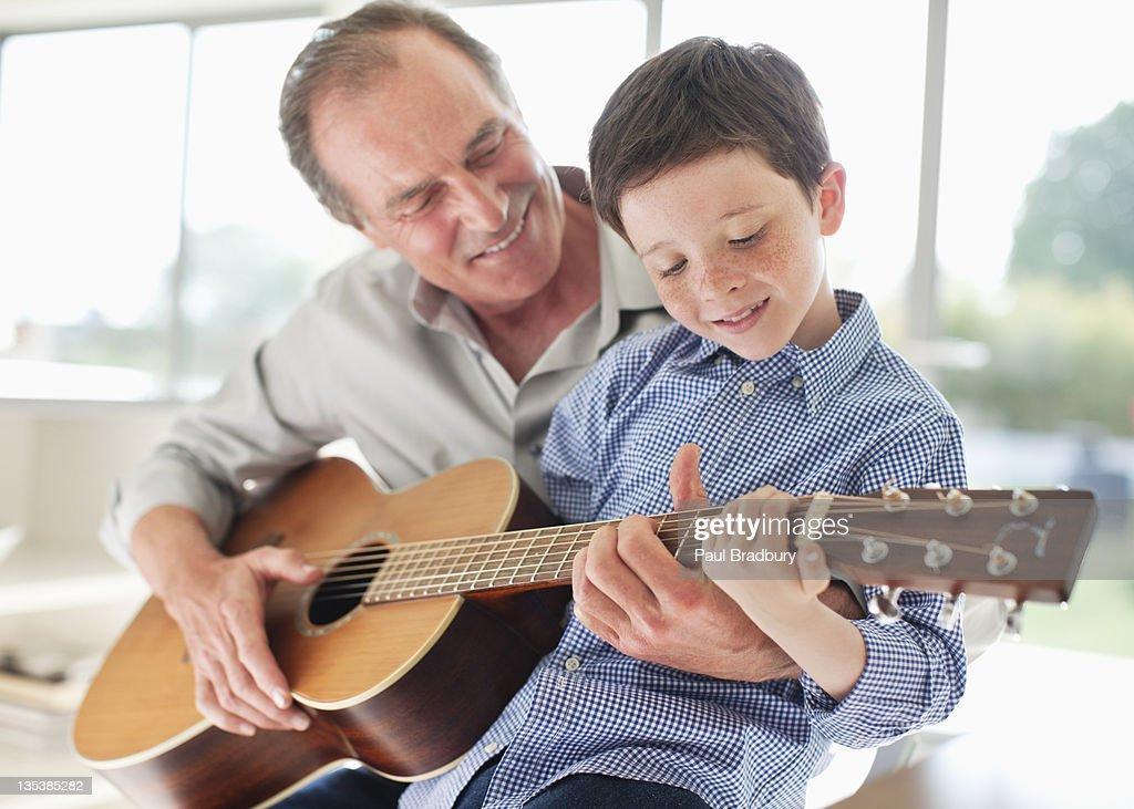 Großvater Unterricht Enkel zu Spielen der Gitarre : Stock-Foto