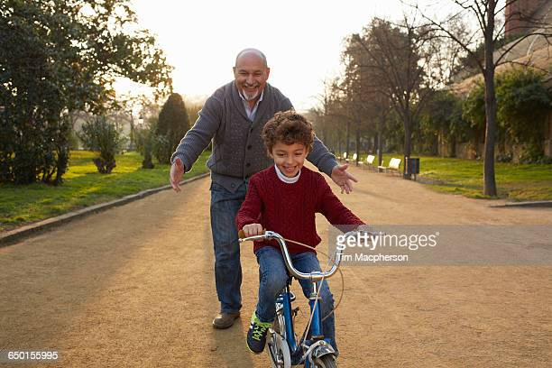Grandfather teaching grandson to ride bicycle in park