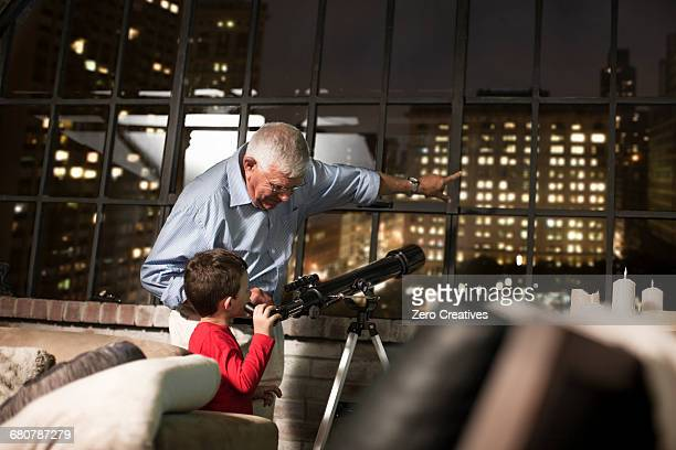 Grandfather teaching grandson to use telescope at home