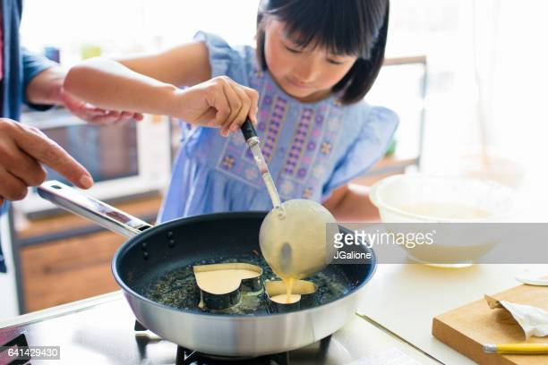 Grandfather teaching his grandaughter to cook