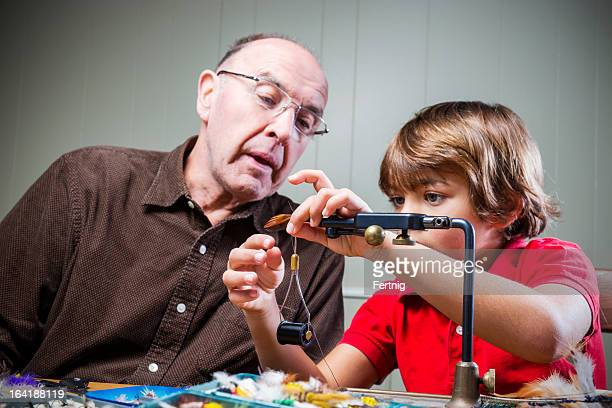 Grandfather teaching his grandchild how to tie fly-fishing flies