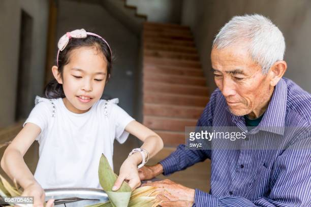 Grandfather  teaching his granddaughter wrapping Zongzi.