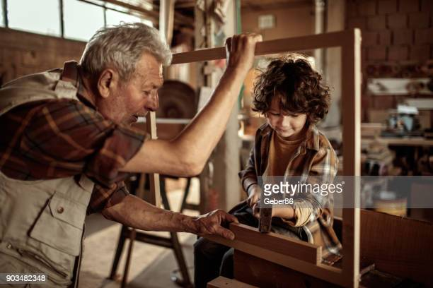 grandfather teaching his grandson - design occupation stock pictures, royalty-free photos & images